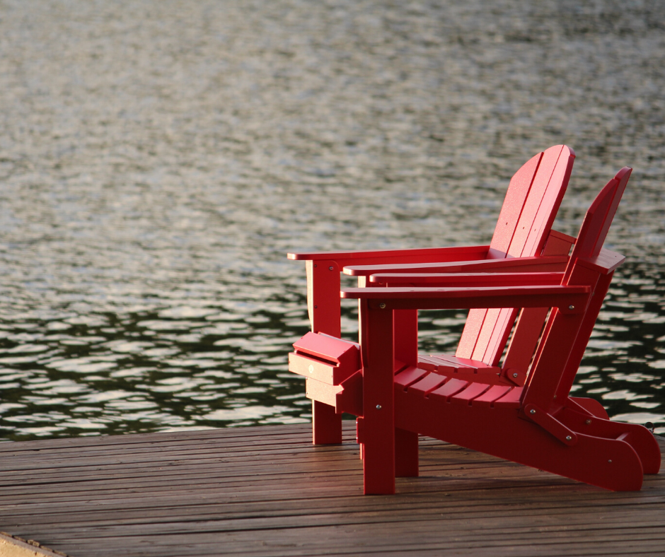 two red chairs on a dock
