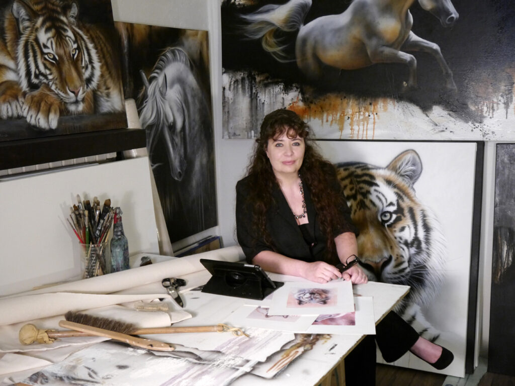 Sandi Baker sitting at her work table in front of artwork